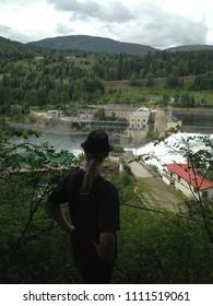 Hippie dude overlooking hydro dam in the Kootenay Mountains