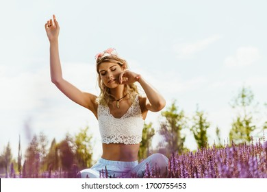hippie girl sits in flowers against a blue sky and meditates