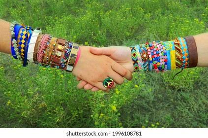 Hippie style friends girls handshake with handmade bracelets, baubles, rings and pacific symbols. Boho fashion lifestyle