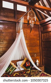 Hippie style wooden room with traditional bed covered by colorful blanket with ornament. Hanging baldachin and dreamcatcher