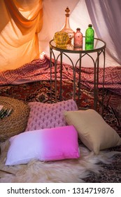 Hippie tent with bright pillows, carpet, tables and colored bottles