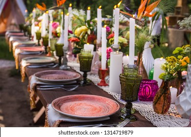 Hippie wedding table decoration with bright flowers, color plates and candles