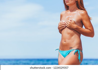 Hippie young ginger woman sunbathing topless on a beach, using suntan cream