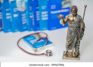 Hippocrates statue  on blured medical books  and stethoscope background