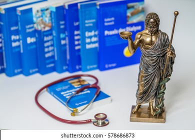 Hippocrates statue and stethoscope on blurred medical books background