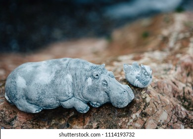 Hippo(hippopotamus) and mandarin duck stone figures relaxing on pink stone
