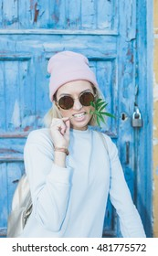 Hippy girl in hat holding a marijuana leaf in the mouth and wearing retro sunglasses, leaning on the old door.. Soft lights, street style.