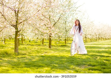 A hippy girl with white dress and floral wreath moves on her white bicycle in the midst of blossoming cherry trees.