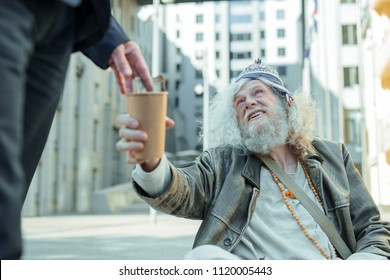 Hippy man. Elderly smiling hippy man sitting on the street near famous business center asking for money or any help