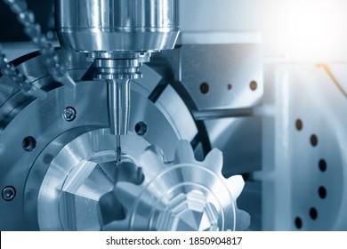 Das hochpräzise 5-achsige Bearbeitungszentrum schneidet die metallenen Getriebe. Hochtechnologie-Teileherstellung durch mehrachsige CNC-Fräsmaschine.