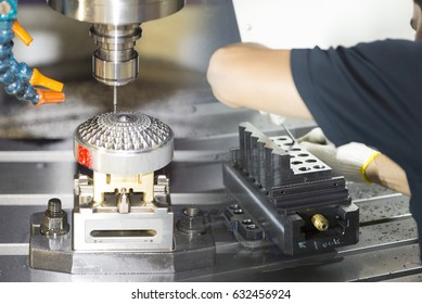 The hi-precision CNC machine cutting mold part and the operator working on the vise.The work shop machining process concept