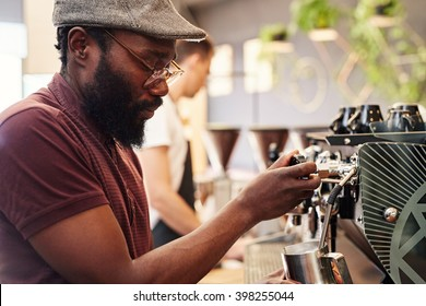 Hipster Afro man working an espresso machine in coffee shop
