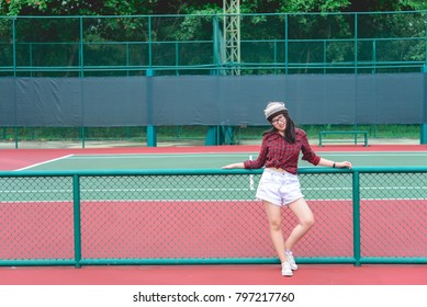 Hipster asian girl pose for take a photo,Fashion portrait pretty woman at tennis court,lifestyle of modern teenage thai girl,show middle fingers
