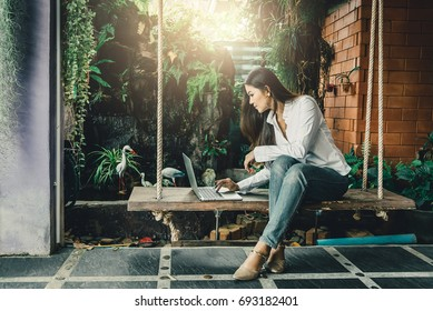 Hipster asian woman relaxing and using laptop on wooden swing in the corner of garden, Smart working woman concept