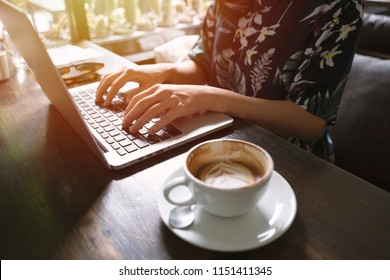 Hipster asian woman using laptop in the cafe with sunlight, lifestyle concept