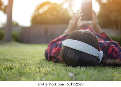 Hipster Asian woman wearing red tone shirt holding smartphone and listening the music by white earplug while lying on the green grass for relaxing with booked of tree and lens flare