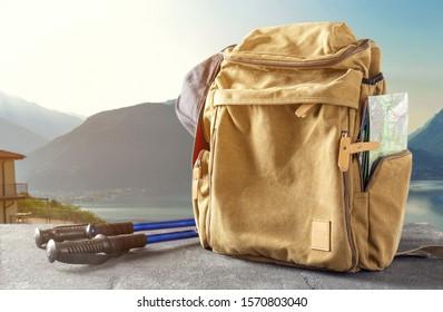 Hipster-Rucksack mit Karte und Trekking-Wanderstock auf dem Tisch auf dem Hintergrund der Berge. Bergwandern