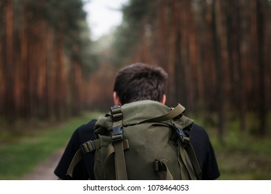 Hipster. Backpacker walking in the forest. Selective focus on the green military backpack. Red pine trees in the background. Vintage photo.