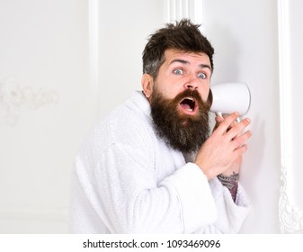 Hipster in bathrobe on shocked face secretly listen conversation. Secret and spy concept. Man with beard and mustache eavesdrops using mug near wall. Man in white interior spying, eavesdropping