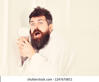Hipster in bathrobe on shocked face secretly listen conversation. Secret and spy concept. Man with beard and mustache eavesdrops using mug near wall. Man in white interior spying, eavesdropping.
