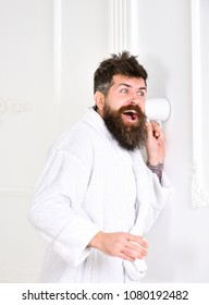 Hipster in bathrobe on surprised face secretly listen conversation. Secret and spy concept. Man in white interior spying, eavesdropping. Man with beard and mustache eavesdrops using mug near wall.