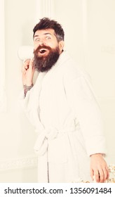 Hipster in bathrobe on surprised face secretly listen conversation. Secret and spy concept. Man with beard and mustache eavesdrops using mug near wall. Man in white interior spying, eavesdropping.