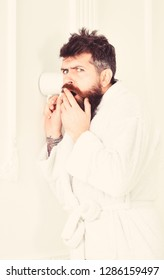 Hipster in bathrobe on suspicious face secretly listen conversation. Secret and spy concept. Man in white interior spying, eavesdropping. Man with beard and mustache eavesdrops using mug near wall.