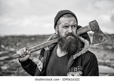 Hipster with beard and mustache on strict face carries axe on shoulder, skyline background. Lumberjack with beard in hat looks brutal and manfully. Lumberjack concept. Man, bearded woodsman with axe.
