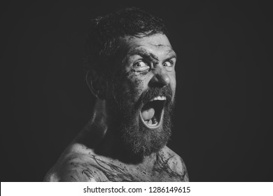 Hipster with beard, mustache shout with horror on black background. Bearded man with tattoo on chest skin. Wizard, sorcerer, warlock. Magic, enchantment, witchcraft. Halloween holidays celebration