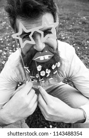 Hipster with beard on cheerful face, posing with star shaped glasses and lips. Guy looks nicely with daisy flowers in beard. Photosession concept. Man with beard and mustache, green background.