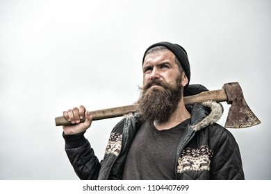 Hipster with beard on serious face carries axe on shoulder sky on background, copy space. Lumberjack brutal and bearded holds axe. Brutal lumberjack concept. Man in hat and warm jacket looks brutally