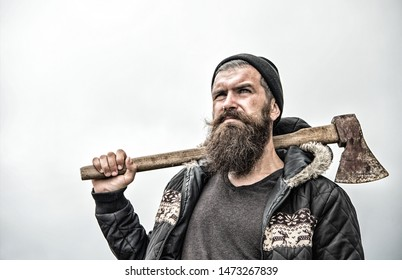 Hipster with beard on serious face carries axe on shoulder sky on background, copy space. Lumberjack brutal and bearded holds axe. Brutal lumberjack concept. Man in hat and warm jacket looks brutally.