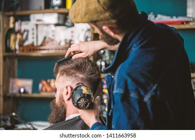 Hipster bearded client getting hairstyle. Barber with hairdryer drying and styling hair of client. Barber with hairdryer works on hairstyle for bearded man, barbershop background. Styling concept.