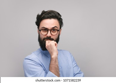 Hipster bearded guy in eyeglasses touching chin in consider looking at camera.