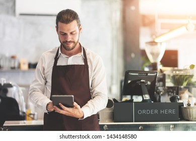 Hipster bearded Male barista holding and looking at digital tablet at the coffee shop or restaurant cafe. Startup of small business owner. entrepreneur, SME.
