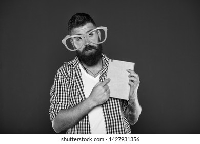 Hipster bearded man funny eyeglasses hold notepad or book. Read this book. Comic and humor sense. Courses adult education. Self education concept. Literary club. Reading book as hobby. Study is fun.