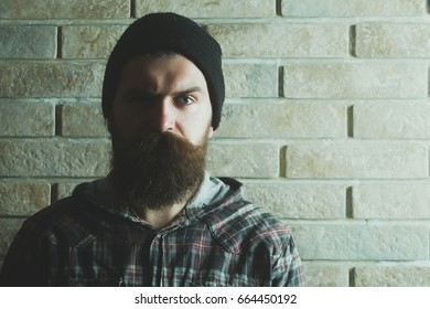 hipster or bearded man with long beard and moustache with serious face posing in stylish black hat and plaid jacket on grey brick wall.
