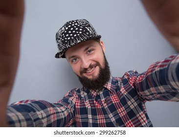 dbf9d238fc626 Hipster bearded man making selfies isolated on grey background. Handsome man  in trucker hat smiling