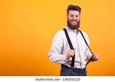Hipster bearded man pulling his lederhosen over yellow background, Man smiling. Looking at the camera. Stylish man.