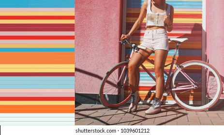 Hipster with bicycle. Girl with light pink bicycle. Woman is standing near pink wall and colorful roller shutters. Urban style. Sport girl. Summer time. Lifestyle. Bright colors. Urban blogger.