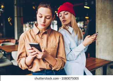 Hipster blogger spying online chat on smartphone of friend.Addicted best friends in casual outfit ignoring live communicating while spending leisure time in social networks on modern cellulars