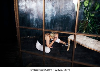 Hipster bride. Blonde woman in keds sits on the floor and gets her face ready for make-up looking in an old mirror