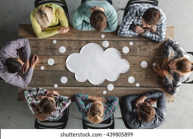 Hipster business teamwork brainstorming planning meeting concept, people sitting around the table with white paper shaped like dialog cloud