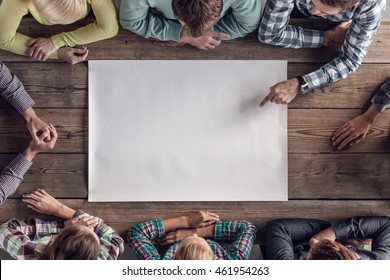 Hipster business teamwork brainstorming planning meeting concept, people sitting around the table with white paper
