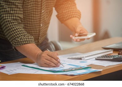 Hipster businessman analyzing investment charts at his workplace and using his smart phone ,stock chart , cellphone, close up vintage stlye