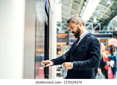Hipster businessman buying a ticket in a machine on subway station.