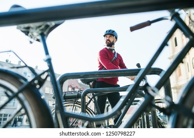 Hipster businessman commuter parking electric bicycle in city when going to work.