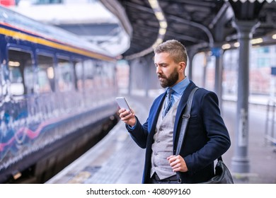 Hipster businessman with smartphone, waiting at the train platfo