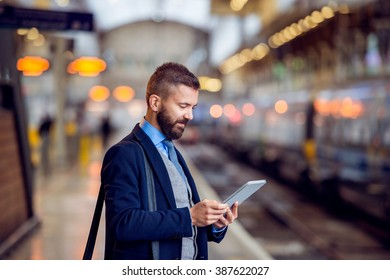 Hipster businessman with tablet, waiting, train platform