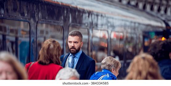 Hipster businessman walking, crowded underground platform, train